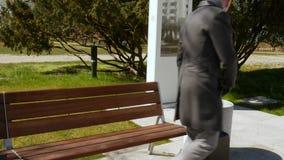 Un giovane elegante in un cappotto grigio con bagagli si siede su un banco, riposante e guardante intorno Viaggio ed affare archivi video