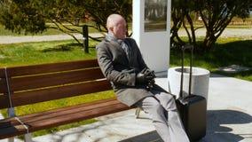 Un giovane elegante in un cappotto grigio con bagagli si siede su un banco, riposante e guardante intorno Viaggio ed affare video d archivio