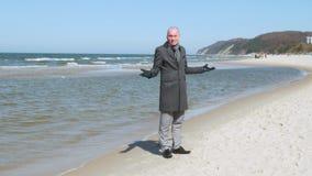 Un giovane elegante in un cappotto sta sulla spiaggia del mare, guarda intorno e sorride - è perso lui non conosce come stock footage