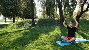 Un giovane in un'erba verde di Lotus Position Sitting On The nel parco il concetto di calma e della meditazione Mani in video d archivio