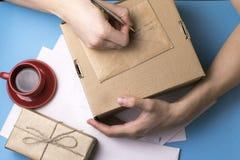 Un giovane esamina e firma la lettera Il concetto di corrispondenza fotografia stock