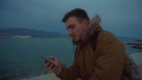Un giovane esamina il theophone contro lo sfondo del mare archivi video