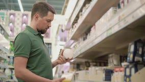 Un giovane esamina una lampadina, lui vuole conoscere quanto watt là è archivi video