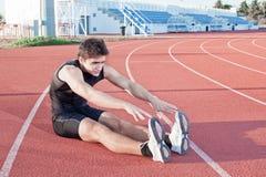 Un giovane fa un allungamento dell'atleta. Immagine Stock Libera da Diritti