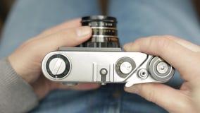 Un giovane fotografo cambia le regolazioni di una macchina da presa sovietica d'annata, fuochi e prende un'immagine Primo piano stock footage