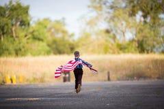 Un giovane funzionamento con una bandiera americana, gioia del ragazzo di essere un americano Immagini Stock