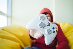 Un giovane gamer mostra una fine bianca della leva di comando di gioco del gamer su Video giochi di concetto Immagine Stock Libera da Diritti