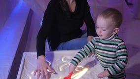 Un giovane genera i giochi con suo figlio in una stanza del sale Riuniscono i modelli su una tavola luminosa video d archivio