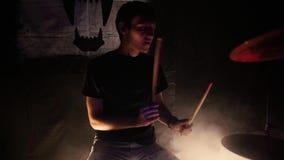 Un giovane gioca i tamburi per una prestazione della banda rock video d archivio