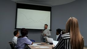 Un giovane impiegato della società in una camicia di bianco riferisce sul progresso del lavoro fatto l'anno scorso e video d archivio