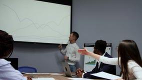 Un giovane impiegato della società in una camicia di bianco riferisce sul progresso del lavoro fatto l'anno scorso e archivi video