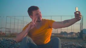 Un giovane in maglietta arancio e jeans dal mare in primavera Il tipo fa una foto sul telefono video d archivio