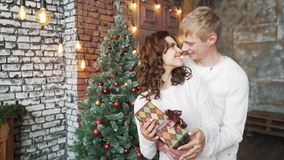 Un giovane in un maglione di bianco dà un regalo alla sua amica Buon anno, Buon Natale archivi video