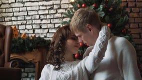 Un giovane marito bello che abbraccia la sua moglie se parte anteriore di un albero, dei presente e dei mandarini del nuovo anno  archivi video