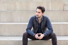 Un giovane maschio caucasico alla moda che si siede sul bleac concreto Fotografie Stock Libere da Diritti