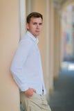 Un giovane maschio premuroso su un fondo urbano Un tipo sicuro e alla moda che indossa l'estate leggera copre concetto di stile Fotografia Stock