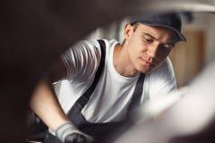 Un giovane meccanico è concentrato sul suo lavoro ad un servizio dell'automobile mentre ripara un'automobile fotografia stock