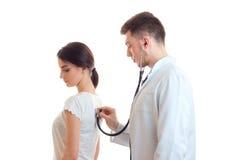 Un giovane medico in uno stetoscopio bianco del cappotto del laboratorio ascolta indietro ragazza immagini stock