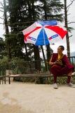 Un giovane monaco buddista tibetano si siede sotto un ombrello in Mcleod Ganj, India Fotografie Stock Libere da Diritti