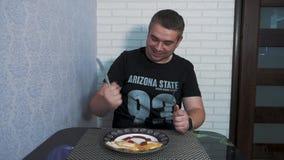 Un giovane nella cucina sta avendo prima colazione archivi video