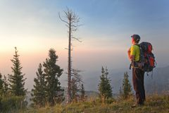 Un giovane nelle montagne al tramonto Fotografia Stock