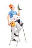Un giovane operaio su una scala che tiene una perforatrice Fotografie Stock