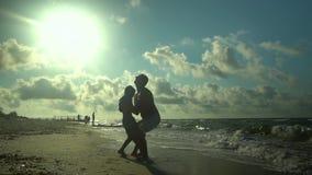 Un giovane padre cammina con suo figlio lungo la spiaggia Il sole splende brillantemente Il papà getta suo figlio nell'aria famig archivi video