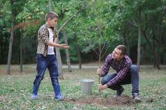 Un giovane padre ed suo figlio stanno piantando un albero nella loro iarda Due ragazzi stanno piantando le piante per la giornata Fotografia Stock
