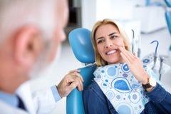 Un giovane paziente visita il dentista perché ha dolore di dente fotografia stock