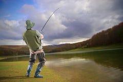 Un giovane pescatore euforico nel lago Mavrovo immagini stock