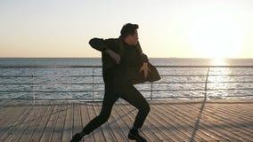 Un giovane popdancer in abbigliamento casual scuro che balla sul ponte di legno di estate, mostra lo stile libero Spiaggia, sole stock footage