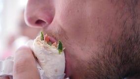 Un giovane, a pranzo morde fuori uno shawarma succoso delizioso, primo piano Movimento lento 1920x1080 HD pieno video d archivio