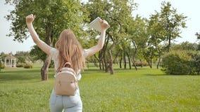 Un giovane ragazza-studente con uno zaino sul suo indietro e le note in sue mani sta camminando nel parco Resto durante lo studio video d archivio