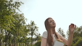 Un giovane ragazza-studente con uno zaino sul suo indietro e le note in sue mani sta camminando nel parco Resto durante lo studio stock footage