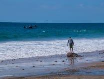 Un giovane ragazzo è stare visto su una roccia sulla spiaggia nell'oceano alla spiaggia di Crystal Cove fotografie stock libere da diritti