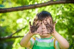 Un giovane ragazzo caucasico che ostenta le sue mani sporche dopo il gioco in sporcizia e sabbia fotografie stock libere da diritti