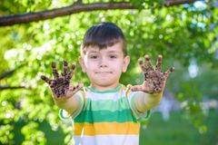 Un giovane ragazzo caucasico che ostenta le sue mani sporche dopo il gioco in sporcizia e sabbia fotografia stock libera da diritti