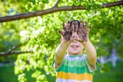 Un giovane ragazzo caucasico che ostenta le sue mani sporche dopo il gioco in sporcizia e sabbia immagine stock libera da diritti
