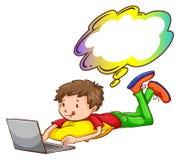 Un giovane ragazzo che per mezzo di un computer portatile Immagine Stock