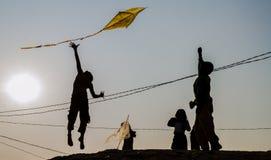 Un giovane ragazzo che salta su per l'aquilone di volo Immagini Stock Libere da Diritti