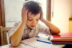 Un giovane ragazzo che si concentra sul compito. Fotografia Stock Libera da Diritti