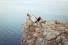 Un giovane ragazzo che si trova sul resto del picco di montagna Fotografie Stock Libere da Diritti