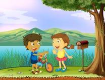 Un giovane ragazzo che tiene una bici e una ragazza vicino ad una cassetta delle lettere di legno Immagine Stock