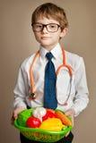 Un giovane ragazzo con la pelle dell'acne in camice tiene un canestro delle verdure Fotografie Stock Libere da Diritti