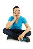 Un giovane ragazzo dell'adolescente sul telefono delle cellule che osserva in su Fotografie Stock