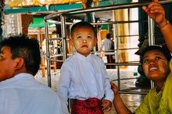Un giovane ragazzo e la sua famiglia in un tempio alla pagoda di Shwedagon in Rangoon Immagine Stock Libera da Diritti