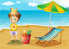Un giovane ragazzo ed i suoi giocattoli alla spiaggia Immagine Stock