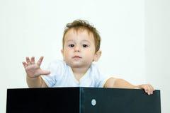 Un giovane ragazzo infantile che dà una occhiata da una scatola su un fondo bianco Immagine Stock