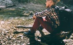 Un giovane resto del viaggiatore sulla banca di un fiume della montagna Immagini Stock