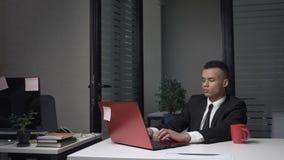 Un giovane riuscito uomo d'affari africano sta sedendosi nell'ufficio, lavorando ad un computer portatile, bevente il caffè da un video d archivio